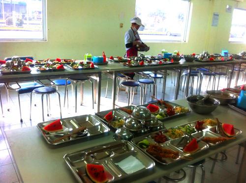 Nhân viên bếp đang chia đồ ăn cho từng suất